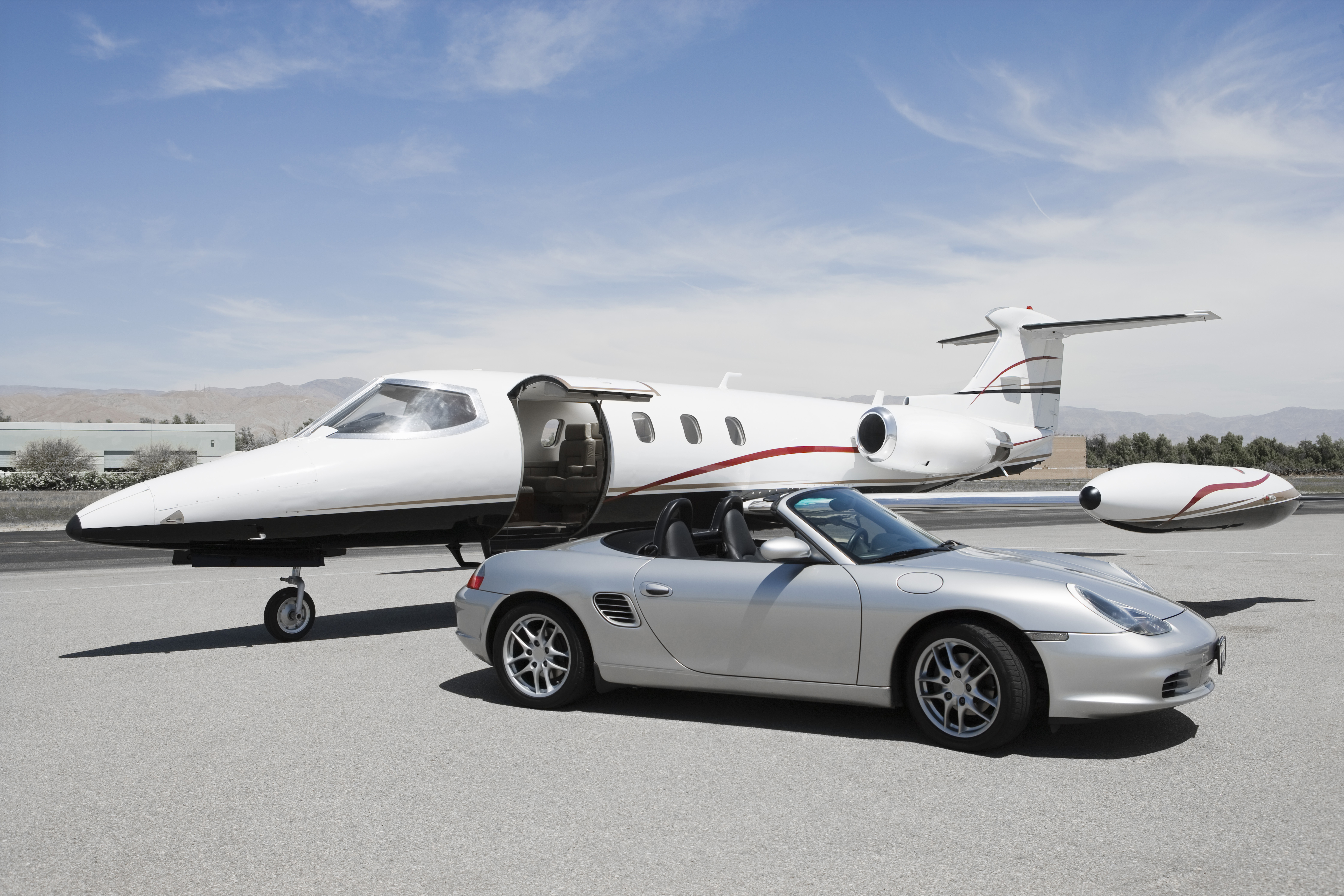 View of a convertible and private jet on landing strip in airpor